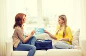 Two smiling teenage girls with plane tickets — Stock Photo