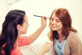 Two smiling teenage girls applying make up at home — Stock Photo
