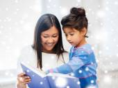 Mother and daughter with book indoors — Stock Photo