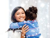 Smiling little girl and mother hugging indoors — Stock Photo
