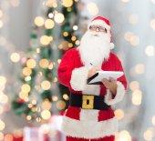 Man in kostuum van de kerstman met Kladblok — Stockfoto