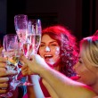 Smiling friends with glasses of champagne in club — Stock Photo #57222721
