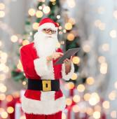 Man in costume of santa claus with tablet pc — Photo