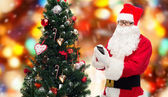 Santa claus with smartphone and christmas tree — Stock fotografie