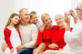Smiling family with camera at home — Stock Photo