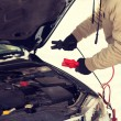 Closeup of man under bonnet with starter cables — Stock Photo #57310715