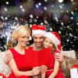 Happy family in santa hats with greeting card — Stock Photo #57311279