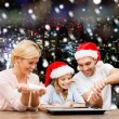 Happy family in santa helper hats cooking — Stock Photo #57311295