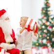 Smiling little boy with santa claus and gifts — Stock Photo #57313729
