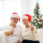 Happy senior couple in santa helper hats — Stock Photo #57314357