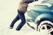 Closeup of man pushing car stuck in snow — Stock Photo