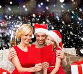 グリーティング カードとサンタ帽子で幸せな家族 — ストック写真
