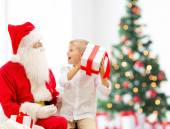 Smiling little boy with santa claus and gifts — Stock Photo