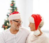 Happy senior couple in santa helper hats — Stock Photo