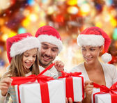 Happy family in santa hats sitting with gift boxes — Stock Photo