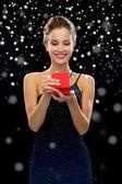 Lächelnde Frau hält rote Geschenkbox — Stockfoto
