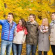 Group of smiling men and women in autumn park — Stock Photo #57321449