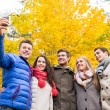 Smiling friends with smartphone in city park — Stock Photo #57321851