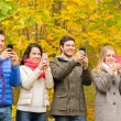 Smiling friends with smartphones in city park — Stock Photo #57322487