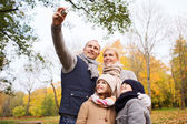 Happy family with camera in autumn  park — Stock Photo