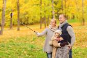 Happy family with smartphone and monopod in park — Stock Photo