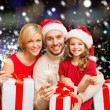 Happy family in santa helper hats with gift boxes — Stock Photo #57345439