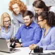 Smiling team with laptop and photocamera in office — Stock Photo #57394145