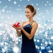 Smiling woman holding red gift box — Stock Photo #57397615
