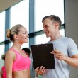 Smiling young woman with personal trainer in gym — Stock Photo #57399787
