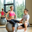 Smiling man and woman with exercise ball in gym — Stock Photo #57399903