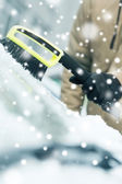 Closeup of man cleaning snow from car — Stock Photo