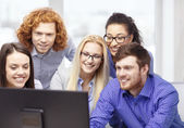 Smiling business team looking at computer monitor — Stock Photo