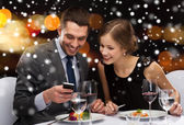 Smiling couple with smartphone at restaurant — Stock Photo