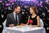 Smiling couple eating dessert at restaurant — Stock Photo