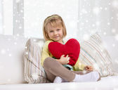 Smiling girl with big red heart sitting on sofa — Stock Photo
