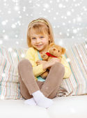 Smiling girl with teddy bear sitting on sofa — Stock Photo