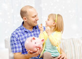 Happy father and daughter with big piggy bank — Foto de Stock