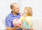 Happy father and daughter with big piggy bank — Stockfoto