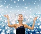 Smiling woman raising hands and looking up — Stock Photo
