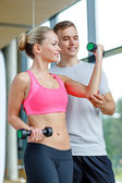 Smiling young woman with personal trainer in gym — Stock fotografie