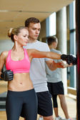 Smiling woman with personal trainer boxing in gym — Stock Photo