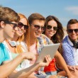 Group of smiling friends with tablet pc outdoors — Stock Photo #57400707