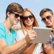 Group of smiling friends with tablet pc outdoors — Stock Photo #57400809