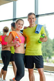 Smiling couple with water bottles in gym — Stock Photo