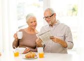 Happy senior couple having breakfast at home — Stock Photo