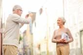 Senior couple photographing on city street — Stock Photo