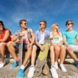 Group of smiling friends sitting on city street — Stock Photo #57451489
