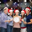Group of teenagers in santa helper hats with clock — Stock Photo #57481591