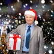 Smiling man in suit and santa helper hat with gift — Stock Photo #57483013