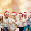 Happy family in santa hats showing thumbs up — Stock Photo #57485587